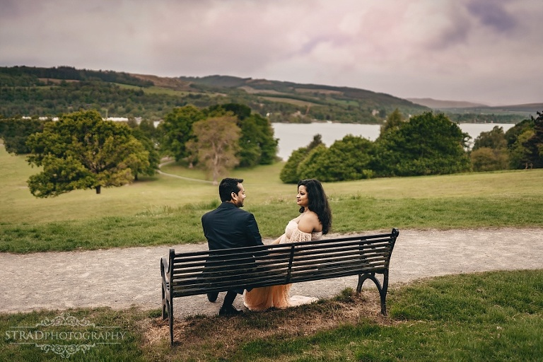Pregnant woman and her thusband sitting at he bench near Balloch Castle