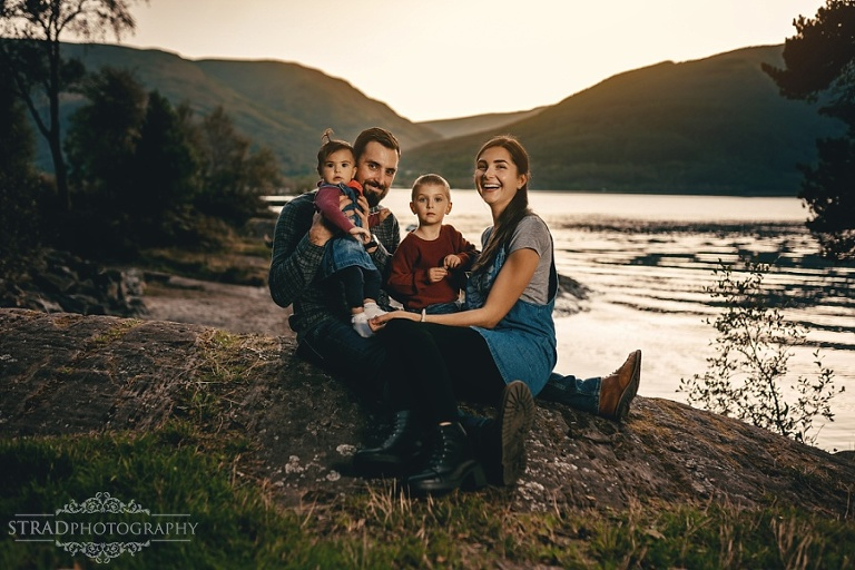 a family of 4 sitting at the loch lomond during sunset