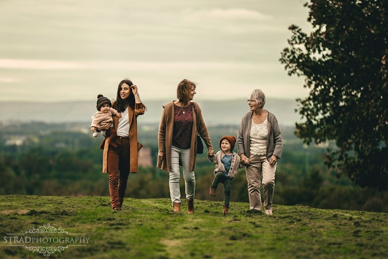 4 generation of women are walking on the grass