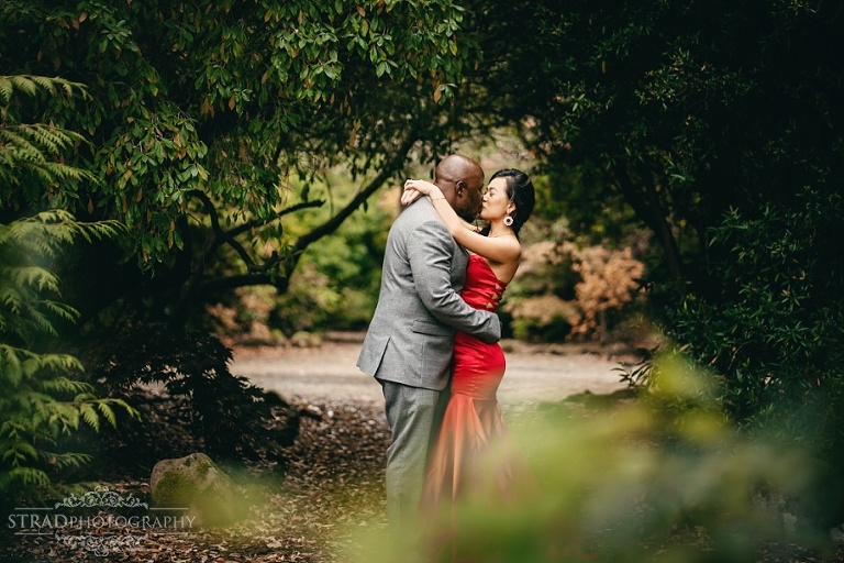Woman in red dress kisses her husband in the garden of Balloch Castle