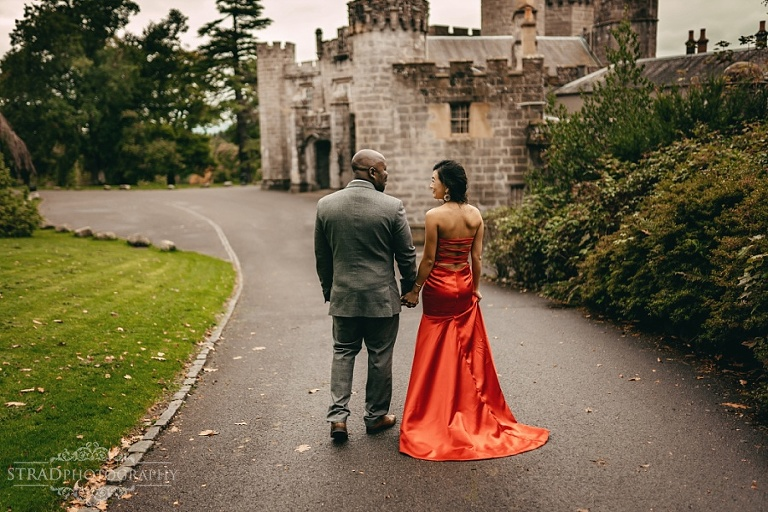 Woman in red dress walks with her husband around Balloch Castle