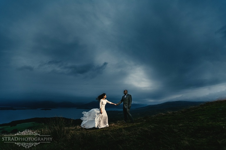 Beautiful dramtic photo of the bride and groom on the top of Conic Hill