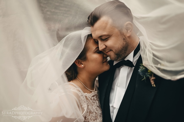 Close portrait of bride and groom under the vale